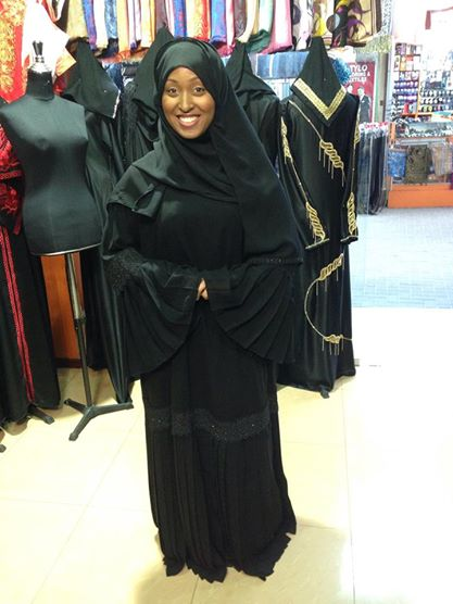 Trying on an abaya for the first time in Bahrain before heading to Saudi Arabia. The hijab is worn around the head, the abaya is worn over the body.